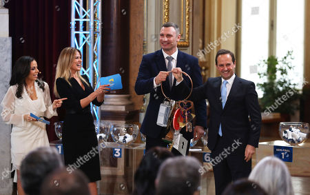 Presenters Filomena Cautela, left, and Silvia Alberto watch as the Mayor of Kiev Vitali Klitschko hands to Lisbon Mayor Fernando Medina, right, a key ring with with keys of former Eurovision Song Contest host cities, at the Lisbon City Hall. Lisbon will host the 2018 Eurovision Song Contest to be held in May