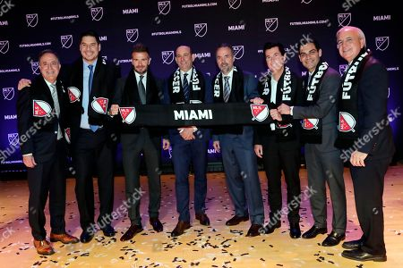 David Beckham, Jorge Mas, Jose Mas, Marcelo Claure, Don Garber, Simon fuller, Francis Suarez, Carlos Gimenez. David Beckham, third from left, poses for a group photo at an event where it was announced that Major League Soccer is bringing an expansion team to Miami, in Miami. From left to right are Jorge Mas, Marcelo Claure, Beckham, MLS Commissioner Don Garber, Jose Mas, Simon Fuller, Miami Mayor Francis Suarez and Miami-Dade County Mayor Carlos Gimenez