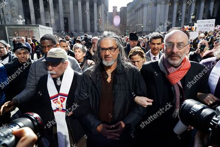 """Ravi Ragbir, center, executive director of the New Sanctuary Coalition, a Trinidad-born immigrant who works to protect New York's immigrant families from detention and deportation, walks with supporters as he arrives for his annual check-in with Immigration and Customs Enforcement (ICE) in New York. A federal judge Monday ordered Ragbir's immediate release from prison Monday saying people subject to deportation deserve """"the freedom to say goodbye."""" She called imprisoned immigration rights activists' treatment """"unnecessarily cruel."""" Ragbir had been detained in an Orange County (N.Y.) correctional facility after ICE officials arrested him during a routine check-in earlier this month"""