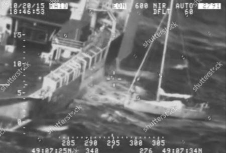 En esta escena de un video proporcionado por la Guardia Costera estadounidense, un francés de pie a la derecha en su velero, con su gato oculto entre su ropa, antes de saltar el martes 20 de octubre de 2015 a un barco que esperaba para rescatarlo, en el sur de Alaska