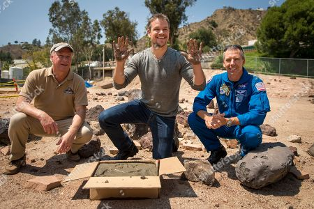 "NASA Journey to Mars and ""The Martian. In this image released by NASA, actor Matt Damon, who stars as NASA Astronaut Mark Watney in the film ""The Martian,"" center, smiles after making his hand prints in cement at the Jet Propulsion Laboratory (JPL) Mars Yard, while Mars Science Lab Project Manager Jim Erickson, left, and NASA Astronaut Drew Feustel look, at the JPL in Pasadena, Calif"