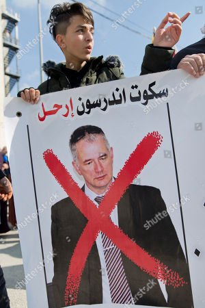 "A protester holds a banner with a defaced picture of Scott Anderson, director of operations for the United Nations Relief and Works Agency, UNRWA, in the West Bank, during a joint protest for UNRWA employees and Palestinian refugees against U.S. funding cuts, in front of the Pa alestinian prime minister's office, in the West Bank city of Ramallah, . Earlier this month, the Trump administration slashed $60 million of a planned $125 million funding installment for 2018. Arabic reads, ""Scott Anderson, leave"