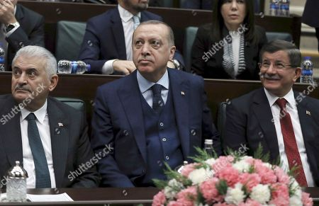 Recep Tayyip Erdogan, Binali Yildirim, Ahmet Davutoglu. Turkey's President Recep Tayyip Erdogan, center, Prime Minister Binali Yildirim, left, and former Prime Minister Ahmet Davutoglu look toward the party members at the parliament in Ankara, Turkey, . Turkish troops and allied Syrian opposition fighters have cleared two villages in a northern Syrian enclave of Syrian Kurdish fighters which Turkey considers to be terrorists. Erdogan said Tuesday that Turkish troops, who had managed to capture the strategic Bursayah hill, northeast of Afrin town, on Sunday, were now attempting to take control of nearby hills and mountains
