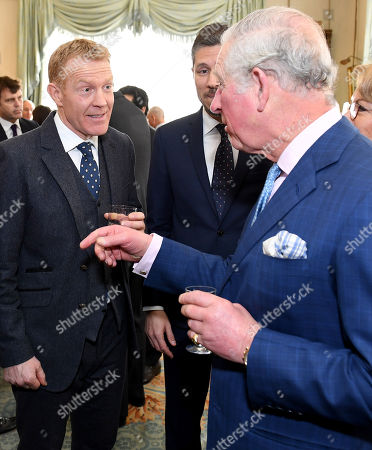 Prince Charles (R) talks to presenter Adam Henson (C) as he hosts a Crop Trust reception