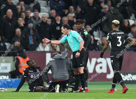 Referee Neil Swarbrick asks Bakary Sako of Crystal Palace to remove himself from the pitch after he sat inches away from the touchline