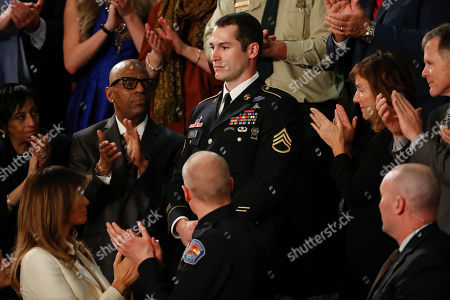 Army Staff Sgt. Justin Peck, center, stands as he's introduced by President Donald Trump during the State of the Union address to a joint session of Congress on Capitol Hill in Washington