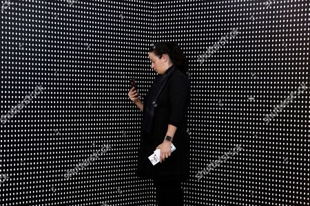 "Janine Fisher of Pittsburgh takes a picture at an art installation called ""Prescribed to Death Memorial"" at the William Pitt Union at the University of Pittsburgh on in Pittsburgh. The installation features 22,000 carved medicine pills that represent the face of someone who fatally overdosed in 2015. A creation of the Illinois-based National Safety Council, the memorial is making its inaugural stop in Pittsburgh through Friday. Future stops will be in Ohio, Oklahoma, Tennessee, Georgia, and New York"