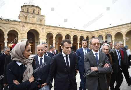 Stock Image of French President Emmanuel Macron (C) stands with Paris' former mayor Bertrand Delanoe (C-R) in the courtyard of the Zitouna mosque in the Medina (old town) of the Tunisian capital Tunis, during Macron's first state visit to the North African country