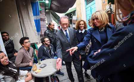 French First Lady Brigitte Trogneux (R) gestures as she talks to youth while touring with Paris' former mayor Bertrand Delanoe (C) in the Medina (old town) of the Tunisian capital Tunis, during Macron's first state visit to the North African country