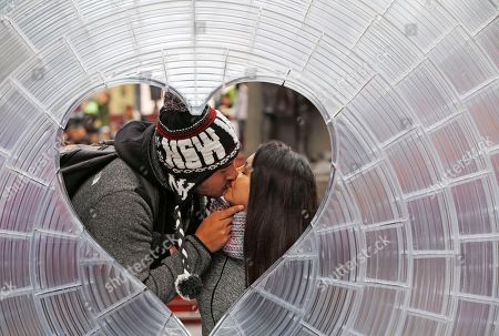 """Guillermo Gutierrez kisses his girlfriend Natalia Gonzalez of Calama, Chile, as seen through """"Window to the Heart,"""" an art installation in Times Square, in New York. Designed by Benjamin Aranda, Chris Lasch, Marcelo Coelho, and Joaquin Bonifaz, the installation is a 12-foot diameter Fresnel lens manufactured with 3D printing to distort and capture the image of Times Square"""