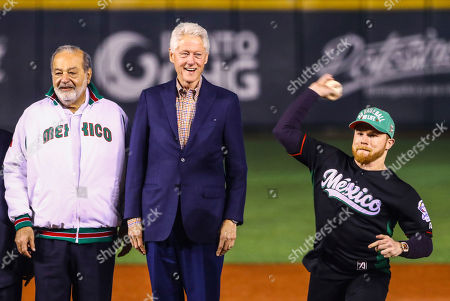 Carlos Slim, Bill Clinton, Saul Canelo Alvarez. Former U.S. President Bill Clinton, center, and Mexican billionaire business magnate Carlos Slim, left, watch as Mexican boxer Saul Canelo Alvarez throws out the first pitch during the opening ceremony of the Caribbean Series baseball tournament in Guadalajara, Mexico
