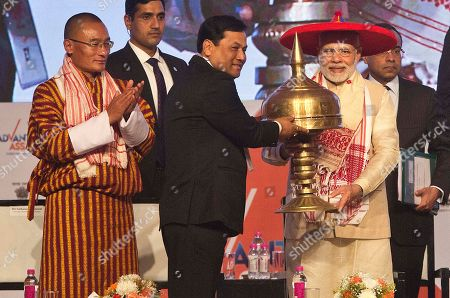 Bhutan's Prime Minister Tshering Tobgay, left, watches as Indian Prime Minister Narendra Modi, right, wearing traditional Japi on his head, is presented an Assamese Sarai by Assam chief minister Sarbananda Sonowal, at the inaugural function of Advantage Assam Global Investor's Summit 2018 in Gauhati, India, . Advantage Assam - Global Investors' Summit is the largest investment promotion and facilitation initiative by the Government of Assam, to highlight geo-strategic advantages of Assam where 16 countries are participating
