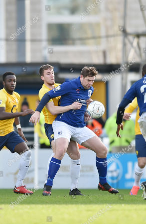 Luke Young of Torquay United battles for the ball with Grant Holt of Barrow, during the Vanarama National League match between Torquay United and Barrow at Plainmoor, Torquay, Devon on February 03