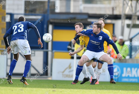 Stock Photo of Luke Young of Torquay United battles for the ball with Grant Holt of Barrow, during the Vanarama National League match between Torquay United and Barrow at Plainmoor, Torquay, Devon on February 03