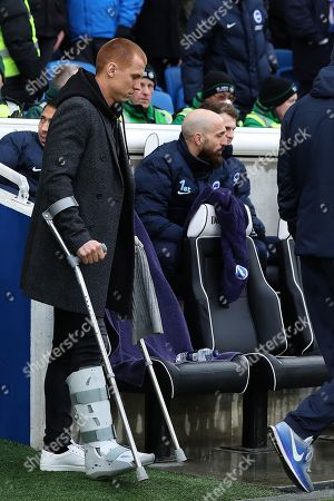 Steve Sidwell on crutches with a protective boot on his right foot makes his way to the stand