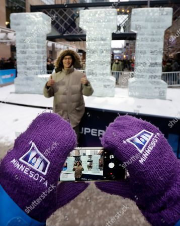 Tara Ivory, Joe Chen. Tara Ivory, a Super Bowl hospitality volunteer, wears Super Bowl mittens as she takes a picture for Joe Chen in front of the Roman numeral LII ice sculpture, in downtown Minneapolis. The New England Patriots and the Philadelphia Eagles are scheduled to play the NFL Super Bowl 52 football game Sunday