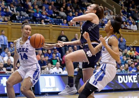 Stock Image of Faith Suggs, Leaonna Odom, Marina Mabrey. Notre Dame's Marina Mabrey drives to the basket while Duke's Faith Suggs (14) and Leaonna Odom defend during the first half of an NCAA college basketball game in Durham, N.C