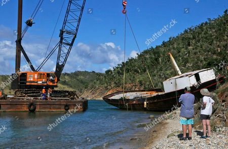 A couple watch as a salvage crew lifts the wreckage of the restaurant and bar Willie T's which was anchored in The Bight Bay off Norman Island in Norman Island, British Virgin Islands, . The boat was damaged by Hurricane Irma which wreaked havoc in parts of the region, including Antigua and Barbuda, Anguilla and St. Martin, the U.S. and British Virgin Islands, Turks and Caicos, the Bahamas and parts of Cuba