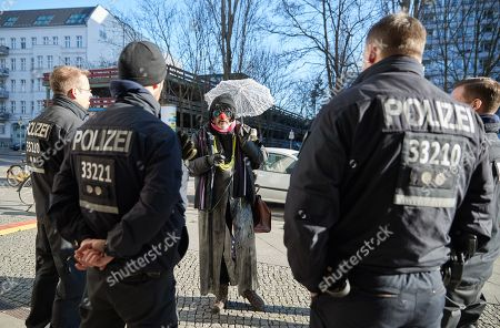 German Police officers stop a 'suspicious' man in a fancy outfit, including a tiny lace parasol, who was approaching the headquarters of Social Democratic Party (SPD), the Willy-Brandt-Haus, where a meeting for the ongoing coalition talks is took place, in Berlin, Germany, 05 February 2018.  The leaders of the Christian Democratic Union of Germany (CDU), the Christian Social Union (CSU) from Bavaria and Social Democratic Party (SPD) met for another round of coalition talks to form a new German government.