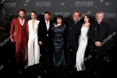 From left to right, Eric Johnson, Rita Ora, Jamie Dornan, E.L. James, a guest, Dakota Johnson, and James Foley pose during a photocall for the world premiere of 'Fifty Shades Freed - 50 Nuances Plus Claires' at Salle Pleyel in Paris