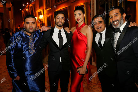 Music producer Naughty Boy, actor Riz Ahmed, model Neelan Gill, comedian Sanjeev Bhaskar and broadcaster Nihal Arthanayake pose for a photograph during a reception for the Britain Asian Trust at Buckingham Palace in London