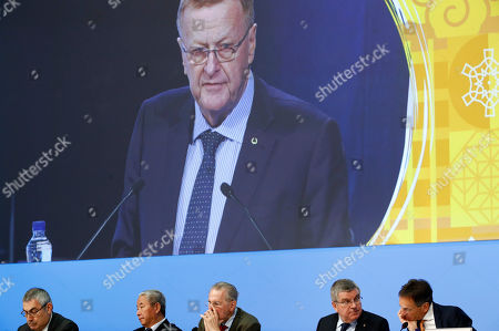Stock Image of John Coates, Christophe De Kepper, Thomas Bach, Zaiqing Yu, Ugur Erdener, Jacques Rogge. International Olympic Committee member and Court of Arbitration for Sport president John Coates is projected on a screen as he delivers a report on the Tokyo 2020 Summer Olympics during the 132nd IOC Session prior to the 2018 Winter Olympics in Pyeongchang, South Korea, . Pictured below Coates are Ugur Erdener of Turkey, from bottom left, Zaiqing Yu of China, former IOC President Jacques Rogge, IOC President Thomas Bach and Christophe De Kepper of Belgium