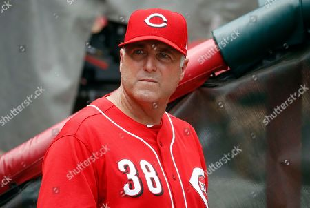 """Cincinnati Reds manager Bryan Price works in the dugout in the ninth inning of a baseball game against the Arizona Diamondbacks in Cincinnati. """"Having a fully healthy Homer Bailey, Brandon Finnegan and Anthony DeSclafani, there's a lot of reason to believe we've finally got there,"""" manager Bryan Price said"""