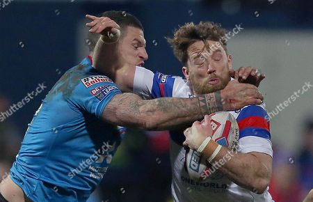 Wakefield Trinity's Danny Kirmond is caught by Salford Red Devils' Luke Burgess