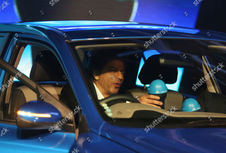 Bollywood super star Shahrukh Khan places newly launched 'Swachh Can' a portable bin, on the dash of a Hyundai Elite i20 car at the Auto Expo in Greater Noida, near New Delhi, India, . The portable bin has been made under Hyundai's corporate social responsibility pillar in support of Indian government's Clean India Mission. The biennial automobile exhibition opens to public Friday and runs till Feb.14