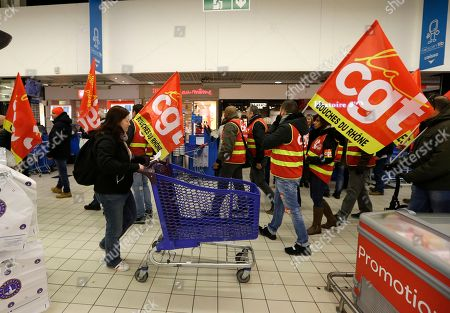 Employees of French retail giant Carrefour Group demonstrate against job cuts with union flags inside a Carrefour hypermarket, in Aix-en-Provence, southern France, . Carrefour CEO Alexandre Bompard announced last month cost savings of 2 billion euros (2.44 billion US dollars) by 2020. CGT union stands for General Working Confederation