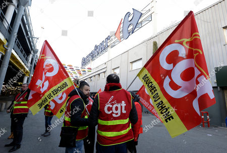 Employees of French retail giant Carrefour Group demonstrate against job cuts with union flags outside a Carrefour hypermarket, in Aix-en-Provence, southern France, . Carrefour CEO Alexandre Bompard announced last month cost savings of 2 billion euros (2.44 billion US dollars) by 2020. CGT union stands for General Working Confederation