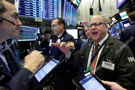 """Trader Jeffrey Vazquez, right, works on the floor of the New York Stock Exchange, . U.S. stocks wavered between small gains and losses in morning trading Friday, giving up some of a big jump that came right after the opening bell. The strong open came a day after the market entered a """"correction"""" for the first time in two years"""