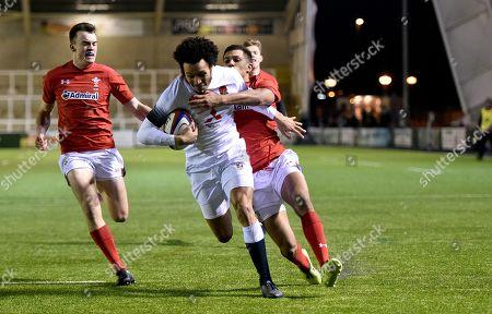 Jordan Olowofela of England U20's scores a try as Ben Thomas of Wales U20's tackles