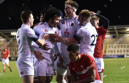 Jordan Olowofela of England U20's scores a try as Ben Thomas of Wales U20's looks dejected