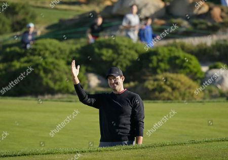 Tony Romo waves after hitting the ball out of a bunker and close to the pin on the 11th green of the Monterey Peninsula Country Club Shore Course during the second round of the AT&T Pebble Beach National Pro-Am golf tournament, in Pebble Beach, Calif