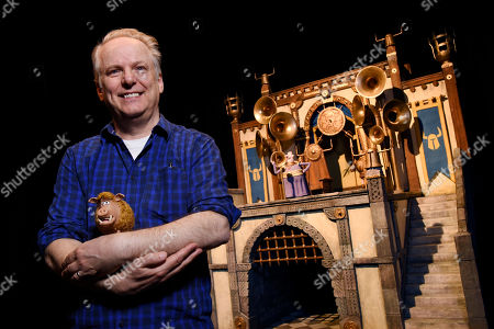 """Nick Park, director of the stop-motion animated film """"Early Man"""" and the voice of the wild boar character """"Hognob,"""" cradles the puppet as he poses in front of the film's Royal Box set at the Beverly Hilton, in Beverly Hills, Calif"""