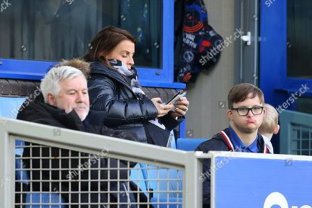 Coleen Rooney looks at her phone as she sits in the stands during the game
