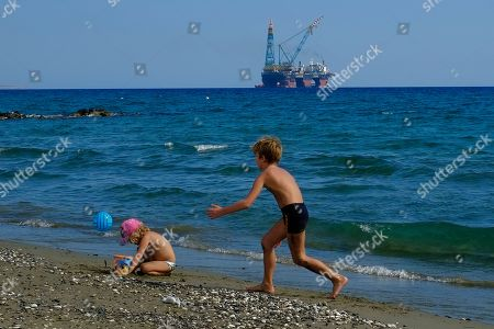 Stock Picture of On children play on a beach with a drilling platform seen in the background, on the outskirts of Larnaca port, in the eastern Mediterranean island of Cyprus. Turkish warships on maneuvers in the Mediterranean Sea have blocked a rig belonging to the Italian energy firm ENI from reaching an area off Cyprus to start searching for gas, officials said Saturday, Feb. 10, 2018. Cyprus' Foreign Minister Ioannis Kasoulides told state broadcaster RIK that the rig has halted its journey heading south of Cyprus and was waiting for directions from ENI. He says Cypriot authorities are in contact with the company and the Italian government
