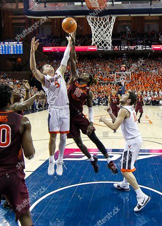 Virginia Cavaliers G #5 Kyle Guy has the ball knocked away by Virginia Tech Hokies G/F #15 Chris Clarke as he goes to the basket during a NCAA Men's Basketball game between the Virginia Cavaliers and the Virginia Tech Hokies at the John Paul Jones Arena in Charlottesville, VA