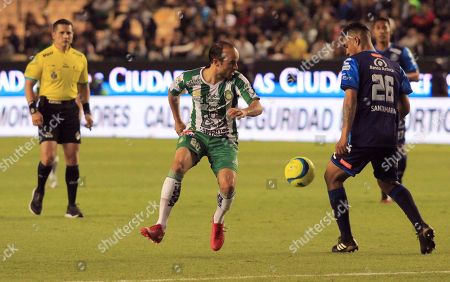Leon's Landon Donovan from the U.S., center, plays the ball against Puebla during a Mexico soccer league match in Leon, Mexico