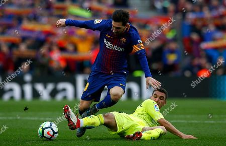 Lionel Messi, Mathieu Flamini. FC Barcelona's Lionel Messi, top, duels for the ball against Getafe's Mathieu Flamini during the Spanish La Liga soccer match between FC Barcelona and Getafe at the Camp Nou stadium in Barcelona, Spain