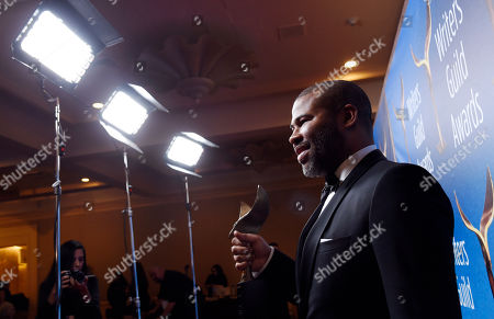 """Jordan Peele, writer/director of the film """"Get Out,"""" poses with his Outstanding Original Screenplay award backstage at the 2018 Writers Guild Awards at the Beverly Hilton, in Beverly Hills, Calif"""
