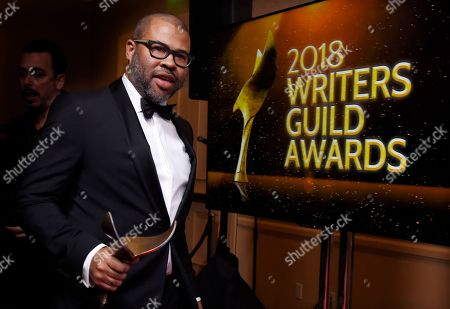 """Jordan Peele, writer/director of the film """"Get Out,"""" arrives backstage carrying his Outstanding Original Screenplay award at the 2018 Writers Guild Awards at the Beverly Hilton, in Beverly Hills, Calif"""