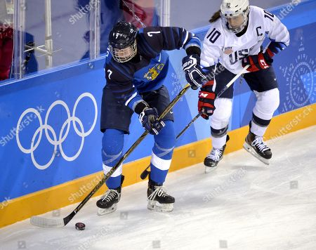 Mira Jalosuo (L) of Finland fights for puck with Meghan Duggan of USA during the women ice hockey preliminary round match Finland vs USA