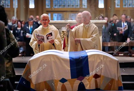 John Spellman, Oliver Duggan, Michael Ryan, J. Peter Sartain. The Rev. Oliver Duggan, right, waves incense over the casket of former Gov. John Spellman, right, and that of his wife, Lois Spellman, both covered in a dual white pall, as the Rev. Michael Ryan, left, and Archbishop J. Peter Sartain sing during the final commendation at a joint funeral Mass for them at St. James Cathedral, in Seattle. The caskets are covered with a John Spellman, the last Republican to serve as Washington's chief executive, died last month at the age of 91. Lois Spellman, his wife of 63 years, died days later
