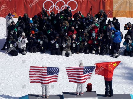 Photographers photograph the venue ceremony with Gold medalist Chloe Kim of the US (C) silver medalist Liu Jiayu of China (R) and bronze medalist Arielle Gold of the US (L) on the podium of the Women's Snowboard Halfpipe final at the Bokwang Phoenix Park during the PyeongChang 2018 Olympic Games, South Korea, 13 February 2018.
