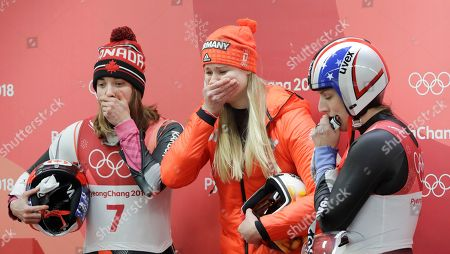 Stock Picture of Silver medalist Dajana Eitberger of Germany, center, watches the final sliders with Kimberley McRae of Canada, left and Erin Hamlin of the United States in the finish area after the women's luge final at the 2018 Winter Olympics in Pyeongchang, South Korea
