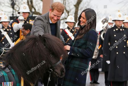 Britain's Prince Harry and his fiancee Meghan Markle meet a Shetland Pony as they arrive at Edinburgh Castle in Edinburgh, Scotland,. The recently engaged couple are on a one day tour to Edinburgh, and will visit the Castle and observe the firing of the One O'clock Gun