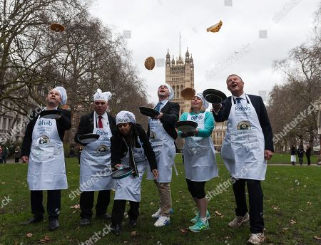 (L-R) Parliament Team members: Paul Scully MP, Bambos Charalambous MP, Dr Rupa Huq MP, Matt Warman MP, Mims Davies MP and Lord St John of Blesto practice flipping their pancakes as they take part in the 21st Parliamentary Pancake Race