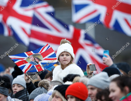 A child carries a British flag with a picture of Britain's Prince Harry and his fiancee Meghan Markle during their visit to Edinburgh Castle, in Edinburgh, Britain, 13 February 2018. Britain's Prince Harry and his fiancee Meghan Markle are on their first official joint visit to Scotland.